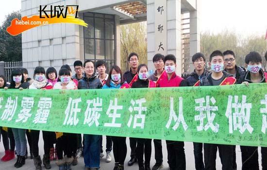 """学生们在""""拒绝雾霾,低碳生活""""活动条幅上签下自己的名字图片"""